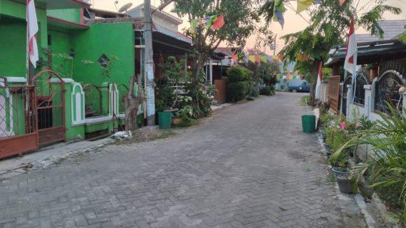 Caption: Rumah keluarga Rakim (paling kiri) bercat hijau, hanya berjarak beberapa langkah dari kediaman Rahayu Dwi Martani (dua dari kanan) dengan gerbang coklat di Jl Imam Bonjol RT 1/RW 16, Mejasem Barat, Kecamatan Kramat, Kabupaten Tegal. Foto diambil 20 Juli 2021.